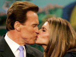 Arnold Schwarzenegger kisses his wife, Maria Shriver,